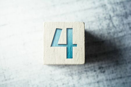 Number 4 On A Wooden Block On A Table