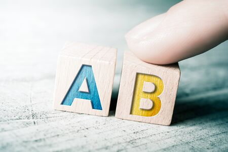 Chance A And B On Wooden Blocks On A Table, A Finger Touches Block A