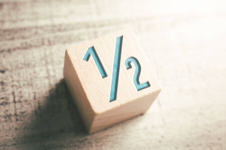 Number Half On A Wooden Block On A Table Stock Photo