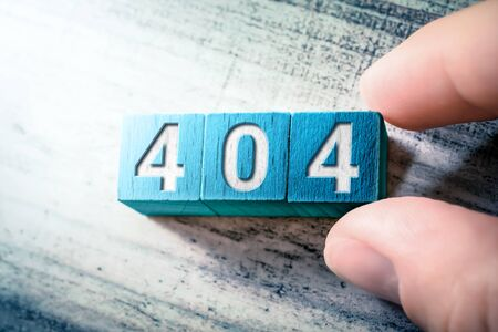 Error Code 404 On Blue Wooden Blocks On A Table, Arranged By A Hand
