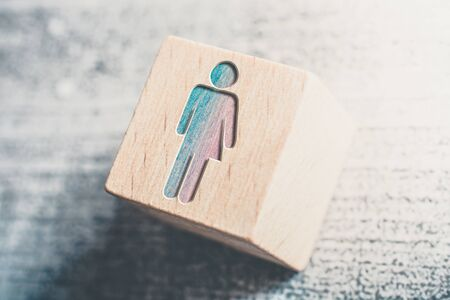 Combined Gender Signs For Male And Female On A Wooden Block On A Table Stock Photo