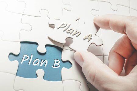 Plan A et Plan B dans le puzzle de pièce manquante, deux doigts tenant le plan d'une pièce