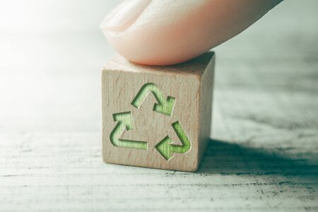 Green Recycling Icon On A Wooden Block On A Table, Touched By Finger
