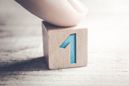 Number 1 On A Wooden Block On A Table Stock Photo