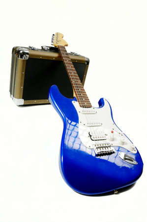 Blue electric guitar isolated on white background bending on amplifier case  photo