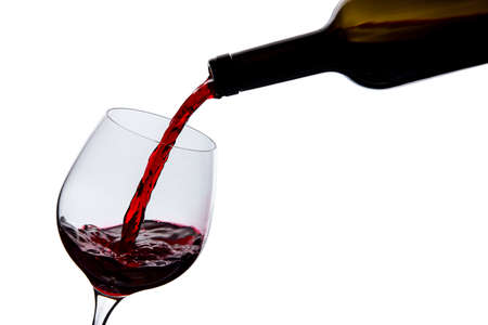 tipple: wine is poured into a glass on a white background