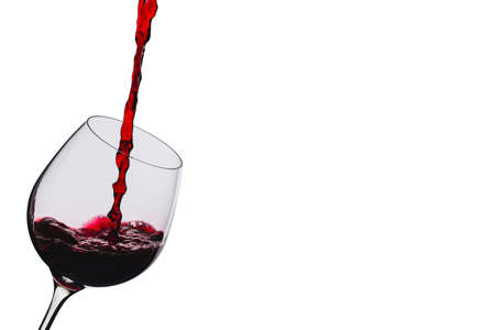 liqueurs: wine is poured into a glass on a white background