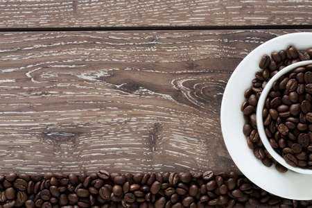 cofe: coffee beans in a white cup on a wooden background