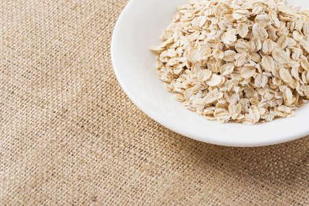 handful: handful of oatmeal in a white plate Stock Photo