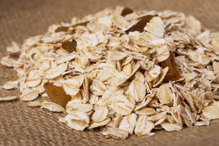 handful: a handful of oatmeal on the background of sackcloth Stock Photo