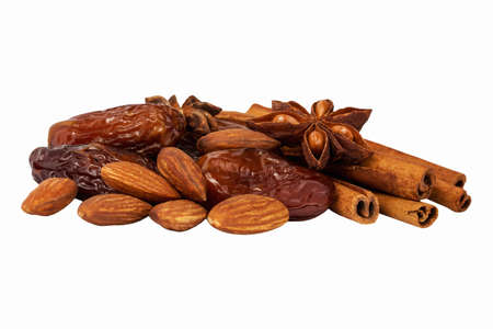 caloric: dates almonds star anise and cinnamon on a white background Stock Photo