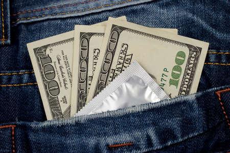 condones: condón y el dinero en un bolsillo de los vaqueros