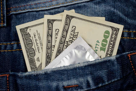 coitus: condom and money in a pocket jeans Stock Photo