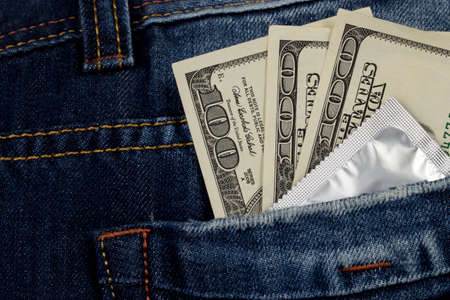 prophylactic: condom and money in a pocket jeans Stock Photo