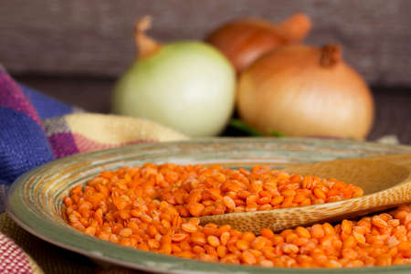 handful: a handful of red lentils in a clay dish