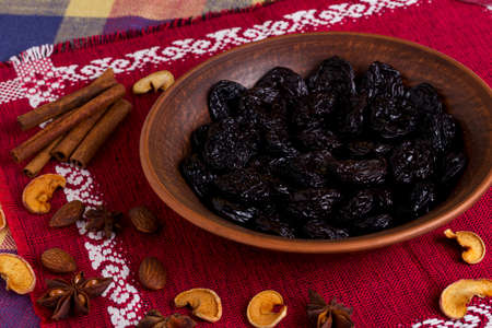 prunes: handful of prunes on a clay plate Stock Photo