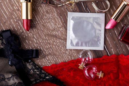 condones: condón y el lápiz labial en un fondo de madera