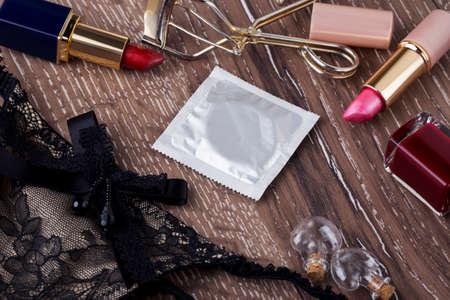Preservativo e rossetto su un fondo in legno Archivio Fotografico - 53356888