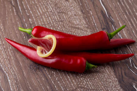 coitus: condom is put on the red chili peppers Stock Photo