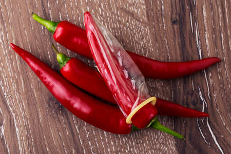 prophylactic: condom is put on the red chili peppers Stock Photo