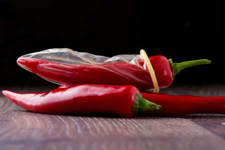 red condom: condom is put on the red chili peppers Stock Photo