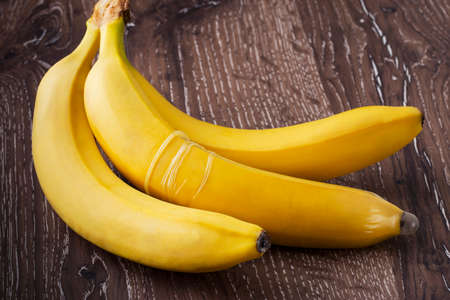 coitus: a condom is put on the banana Stock Photo