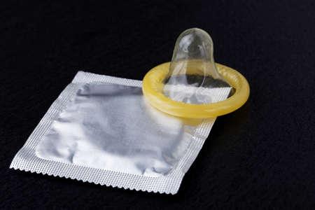 condones: cond�n y el paquete sobre un fondo negro