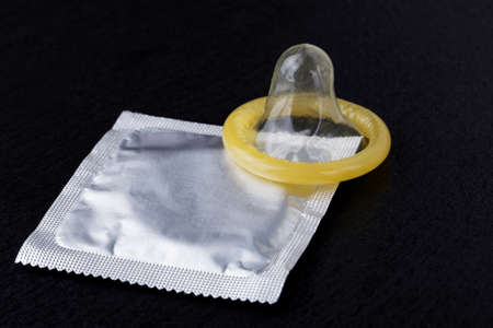 condoms: condom and pack on a black background
