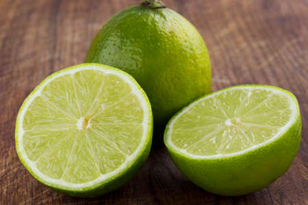 lime: the green lime on a wooden table Stock Photo