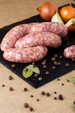 sausage: uncooked sausages on a black cutting board