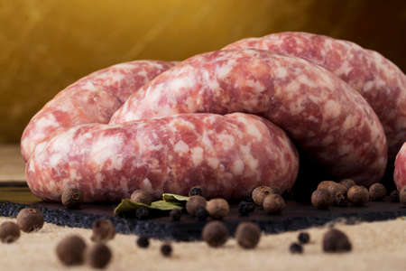 uncooked: uncooked sausages on a black cutting board