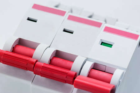 toggle switch: three red electric toggle switch on a wall Stock Photo