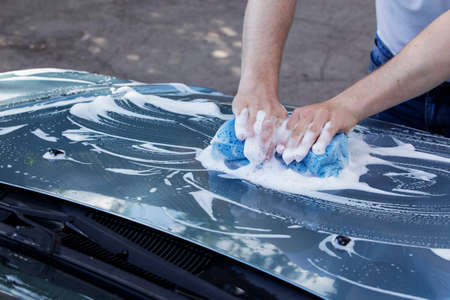 soap suds: a turquoise car is washing in soap suds Stock Photo