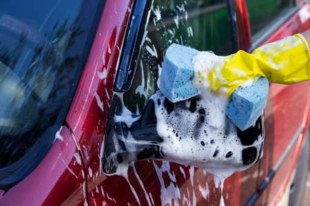 suds: a red car is washing in soap suds Stock Photo