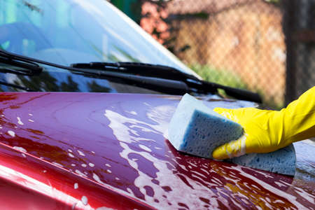 restore: a red car is washing in soap suds Stock Photo