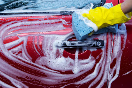 soap suds: a red car is washing in soap suds Stock Photo