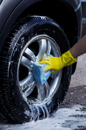 work gloves: car wheel is washing in soap suds Stock Photo