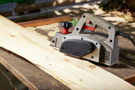 planer: the electric planer is lying on a wooden table Stock Photo