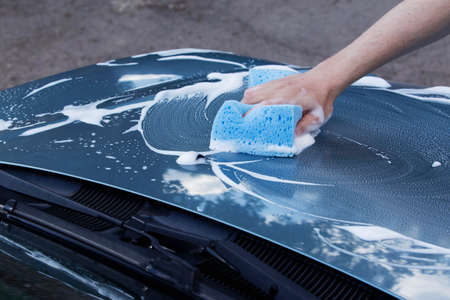 suds: a turquoise car is washing in soap suds Stock Photo