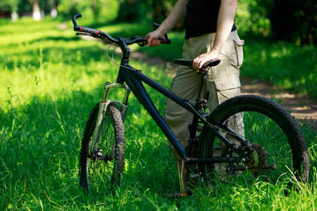 road bike: Young man riding a mountain bike in the woods Stock Photo