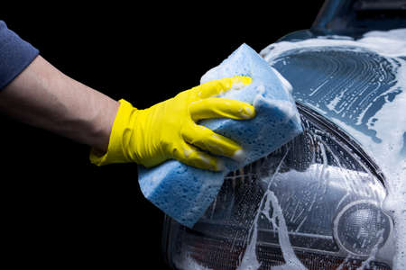 turquoise car is washing in soap suds Stock Photo
