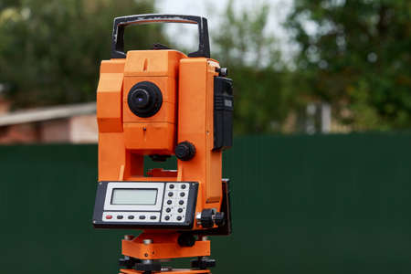 tripod mounted: the orange theodolite is mounting on a tripod