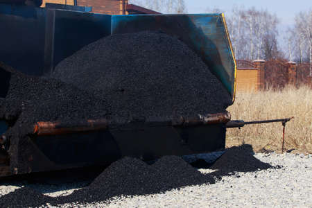 industrial pavement truck laying fresh asphalt on construction site