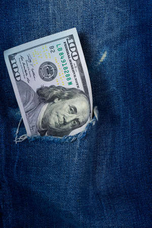 Hundred dollar banknote in a hole of jeans