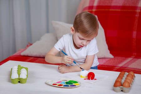 Little boy paints eggs with colored paints