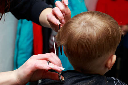 The little boy in the barber shop hair cut by a professional Archivio Fotografico