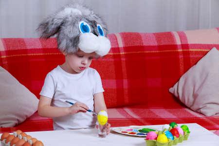 Little boy paints eggs with colored paints in a bunny cap 免版税图像