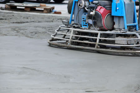 Worker with power tools makes a smooth concrete surface during construction