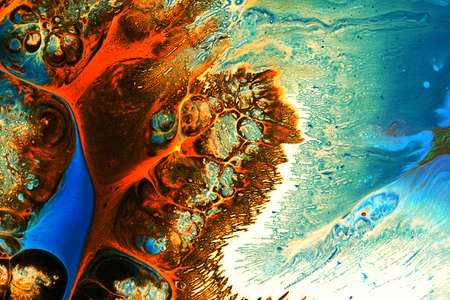Abstract background of acrylic paints in orange and blue color tones
