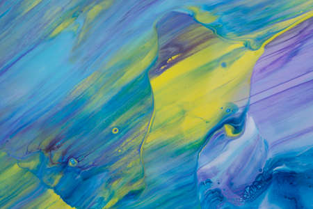 Abstract background of acrylic paint in blue violet and yellow tones
